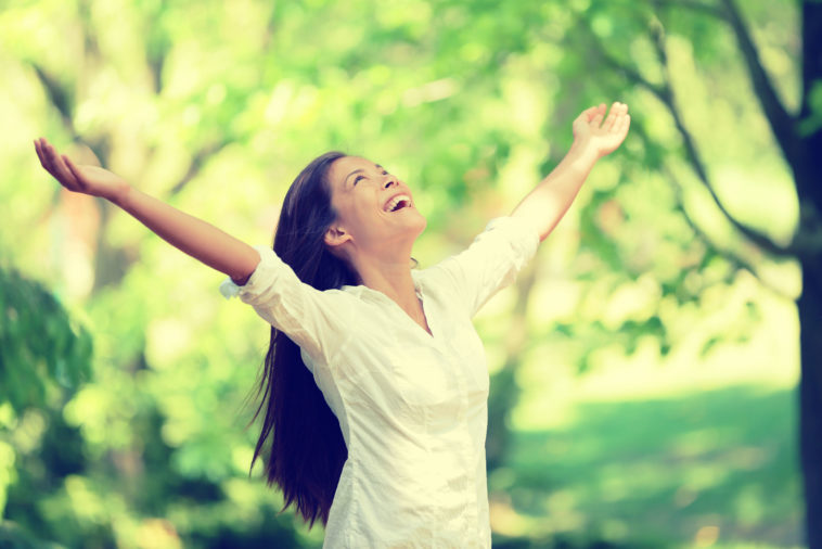 freedom physio happy woman feeling alive and free in nature breathing clean and fresh air. carefree young adult dancing in forest or park showing happiness with arms raised up. spring allergies concept.