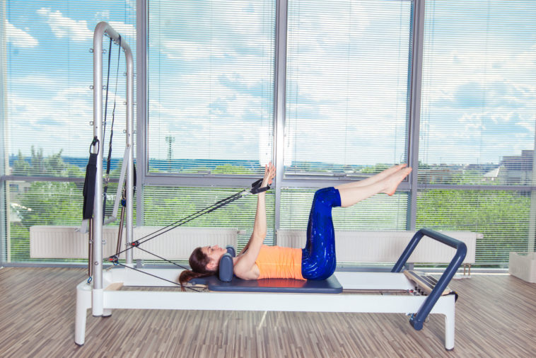 perth pilates reformer workout exercises woman brunette at gym indoor.